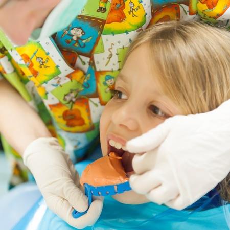 plaster mould: Orthtodontis preparing teeth mold for little girl