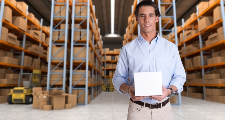 Young man holding a blank white box in a distribution warehouse photo