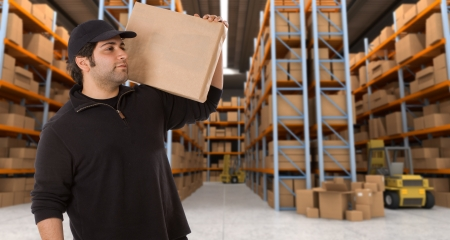 Deliveryman carrying a parcel in a distribution warehouse photo