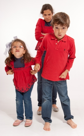 boy barefoot:  Three siblings with very angry expressions  Stock Photo