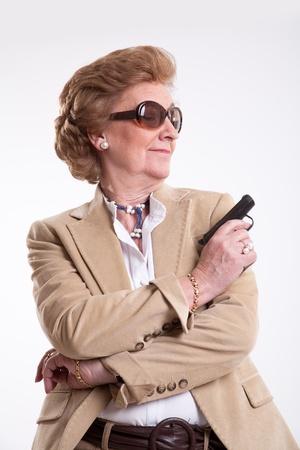 mujer con pistola: Señora madura con gafas de sol y una pistola en la mano Foto de archivo
