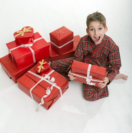 exclaim:  Excited young boy in pajamas surrounded by gift boxes