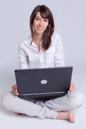 Barefoot young woman using her computer cross-legged on the floor    Stock Photo - 14715290