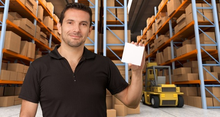 A man holding a blank paper in a distribution warehouse, ideal for inserting your own message photo