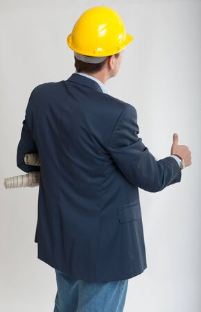 man rear view:  Rear view of a man with a safety helmet consulting blueprints with his thumb up