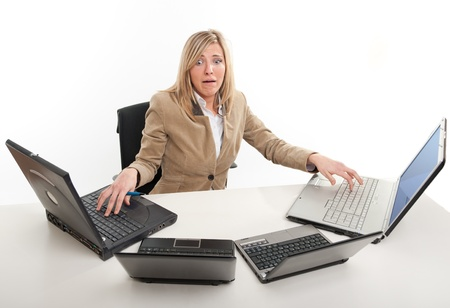 Stressed young woman using four laptops  Stok Fotoğraf