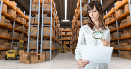 woman inspecting document in warehouse photo