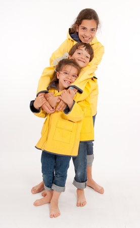 Three young siblings barefoot wearing jeans and yellow raincoats  photo
