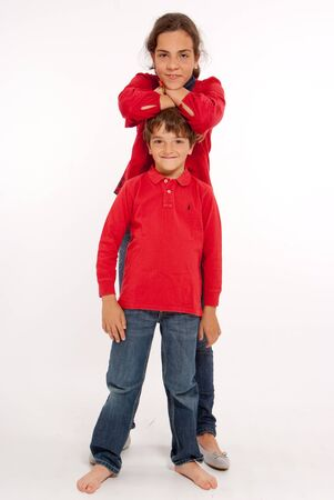 Young brother and sister in red tops and blue jeans  photo