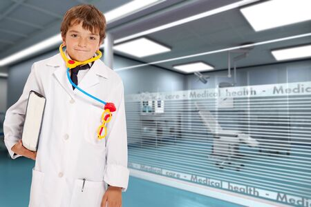 role play: Young boy with a doctors uniform and toy stethoscope holding a book in a hospital interior  Stock Photo
