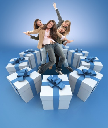 A group of happy celebrating women surrounded by gift boxes photo