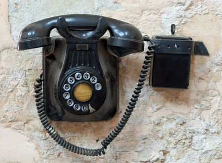 fixed line: Vintage black Bakelite telephone fixed to a wall