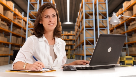 order shipment: Female administrative in a desk with a distribution warehouse in the background Stock Photo