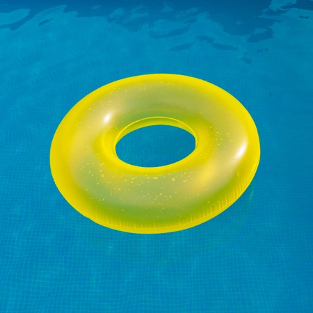 float tube: Bright yellow floater in the middle of the pool