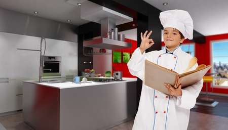 countertop:  Cute young boy dressed as a chef in a modern kitchen holding a book