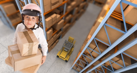 Child wearing a motorbike helmet carrying parcels in a transportation warehouse photo