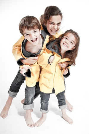 raincoat:  Three young siblings barefoot wearing jeans and yellow raincoats