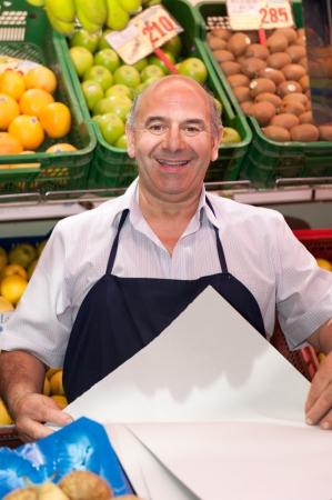 vendedor: Sonriendo verdulero en el puesto del mercado