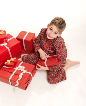 birthday boy:  Young boy in pajamas surrounded by gift boxes  Stock Photo
