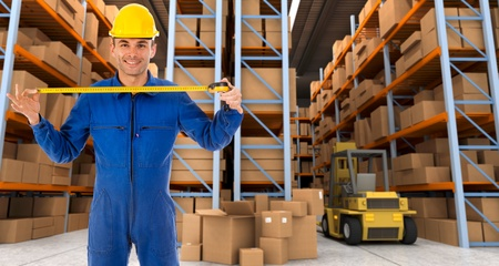 Man with helmet and blue overalls in a distribution warehouse extending a tape measure photo