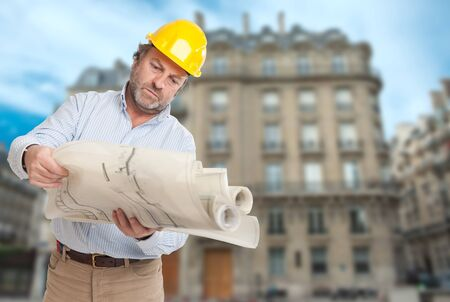 condominium complex: Man with helmet and blueprint and an old Parisian building
