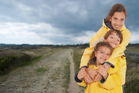 Three happy kids in raincoats on the country photo