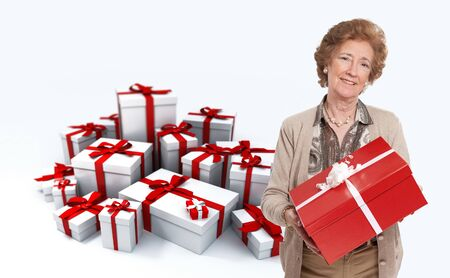 mature woman:  Elegant mature woman holding a present against a background full of gift boxes