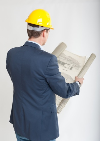 rear view:  Rear view of a man with a safety helmet consulting blueprints  Stock Photo