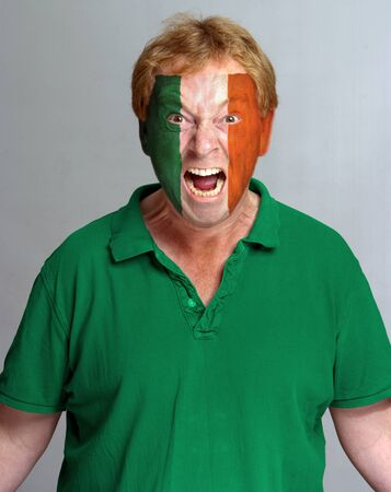 supporter: Hysterical supporter with the Irish flag painted on his face Stock Photo
