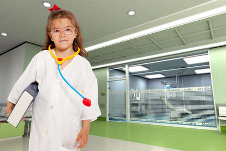 Young girl with a doctor�s uniform and toy stethoscope holding a book in a hospital interior  photo