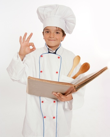 toque:  Cute young boy dressed in chef clothes, holding a book, doing the ok sign