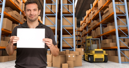 A man holding a blank paper in a distribution warehouse, ideal for inserting your own message Stock Photo - 15616015