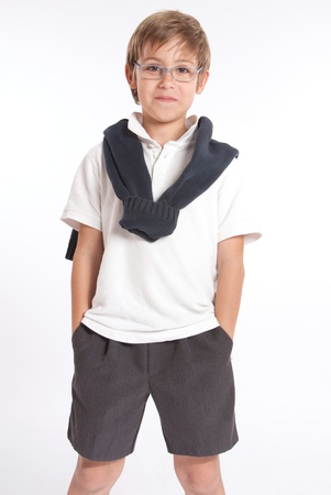 Schoolboy standing with his hands in his pockets photo