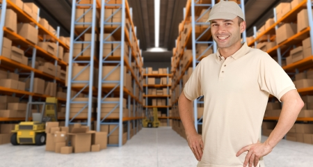 storage warehouse: Deliveryman carrying a parcel in a distribution warehouse