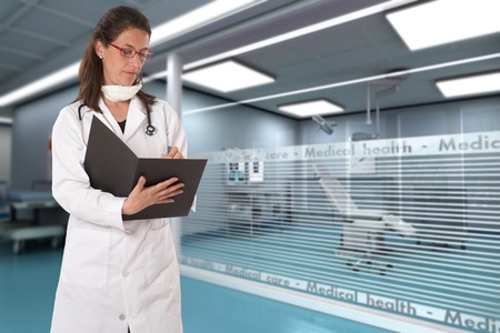 taking notes:  Woman with a medical uniform taking notes in a hospital  Stock Photo