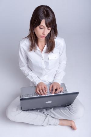 conclusion: Descalzo mujer joven que usa su computadora con las piernas cruzadas en el suelo