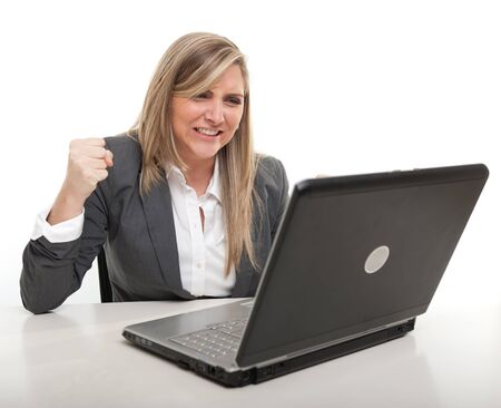 annoy:  Young business woman with an annoyed expression looking at her computer