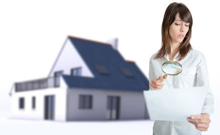 Woman scrutinizing a document with a house in the background photo