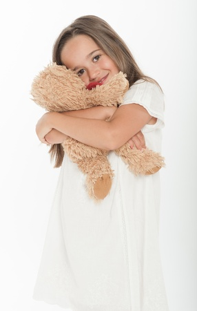 children playing with toys: Cute little girl holding a teddy bear