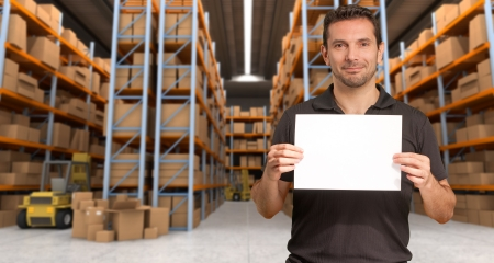 warehouse equipment: A man holding a blank paper in a distribution warehouse, ideal for inserting your own message