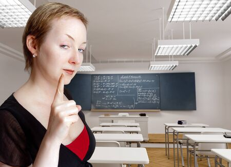 strict:  Strict serious teacher with a warning gesture in a classroom