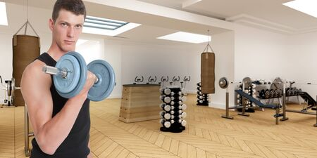 athleticism: Young man in a gym lifting a dumbbell Stock Photo
