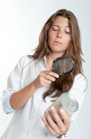 can food: Young woman inspecting an aluminum can through a magnifying glass Stock Photo
