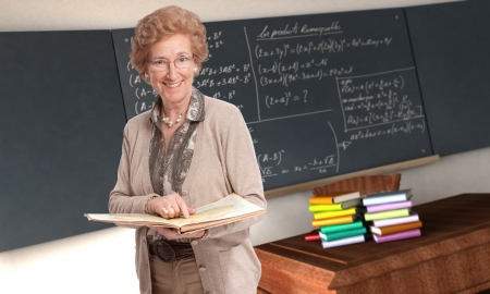 formulae: Friendly mature teacher pointing to a book in a classroom Stock Photo