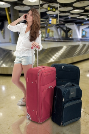 Happy Girl on the phone at the baggage claim at the airport Stock Photo - 15812660