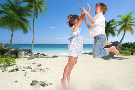 happily:  Little boy and girl happily jumping on a tropical beach