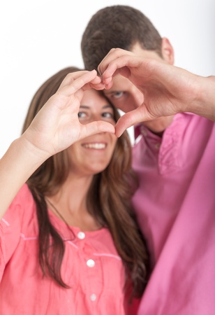 Young couple forming a heart shape with their hands photo