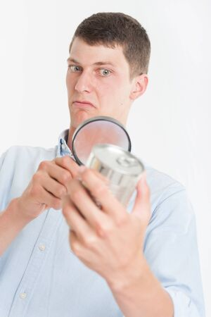 Young man inspecting a cans nutrition label with a magnifying glass  photo