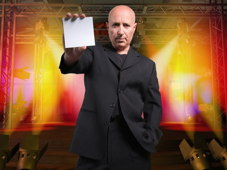 bald spot:  Showman in on a stage, holding a blank note to the camera