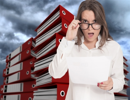 filing documents: Stressed looking woman surrounded by piles of ring binders